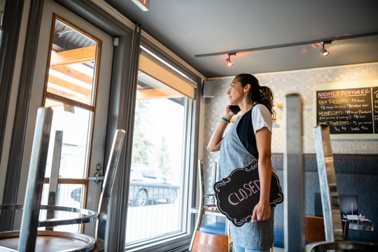 Female business owner with closed sign talking on smart phone in cafe