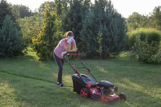Tired woman making a short break while cutting grass with a lawn mower. Outdoor household chores concept.