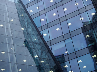 Full frame modern office architecture abstract with geometric angular windows with lights and reflected buildings in blue glass windows Wall mural