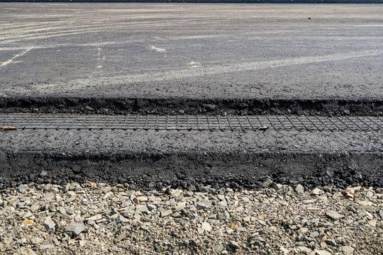 black fine geogrid adhered to bitumen, road construction, fresh asphalt
