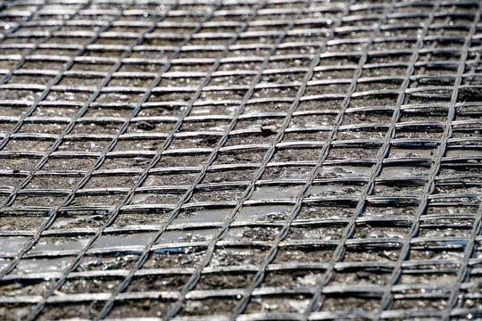 macro fine geogrid adhered to bitumen