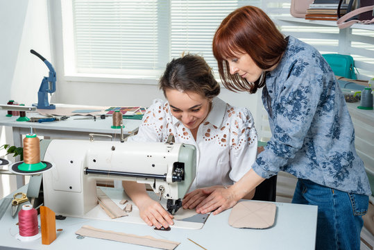 a mentor teaches a student to sew