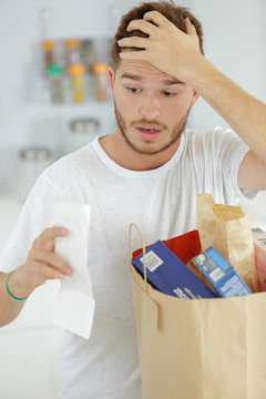 young man looking with shock at shopping receipt
