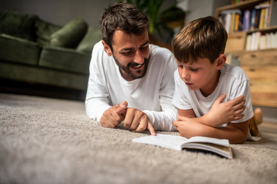 Father and son read a book together, father smiles while son reads, education at home