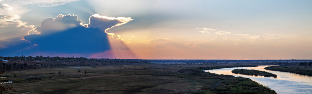 Thunderstorm developing at sunset over the Kavango river valley near Rundu on the border between Naminia (left side of the river) and  Angola (right side).