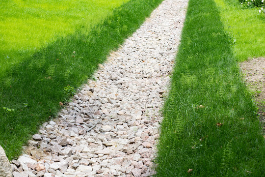 Drainage ditch filled with crushed granite with banks overgrown with lawn grass