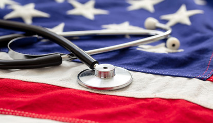 US of America health. Medical stethoscope on a USA flag, closeup view.