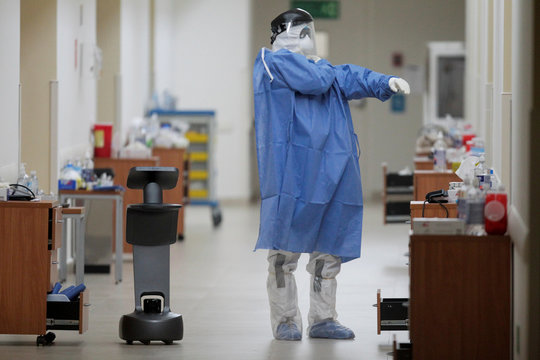 A healthcare worker puts on his protective suit while using a robot to carry out consultations with patients suffering from the coronavirus disease (COVID-19), at NOVA hospital in Monterrey