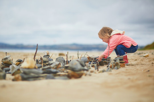 Adorable toddler girl on the sand beach at Atlantic coast of Brittany, France