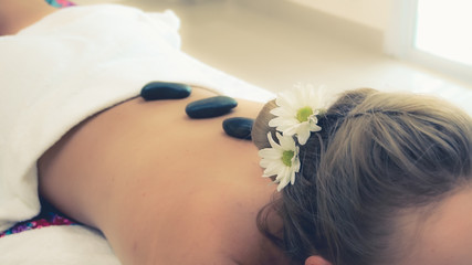 Woman getting hot stone massage treatment by professional beautician therapist in spa salon. Luxury wellness, back stress relief and rejuvenation concept.