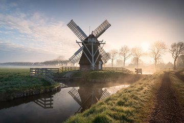 misty sunrise over Dutch windmill