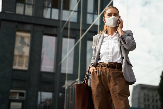 Business during covid 19. Confident business woman wearing protective face mask talking on mobile phone while standing against office building outdoors