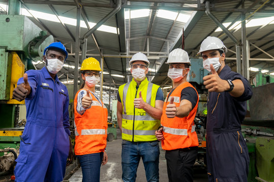 Group of multiethnic engineer with workers giving thumbs up and  wearing surgical mask to prevent covid-19 in manufacturing factory. Successful diverse teamwork standing together in workplace.