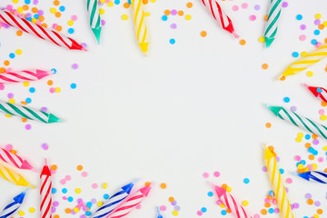 Colorful birthday cake candles with candy sprinkles. Top down view frame on a white background. Copy space.