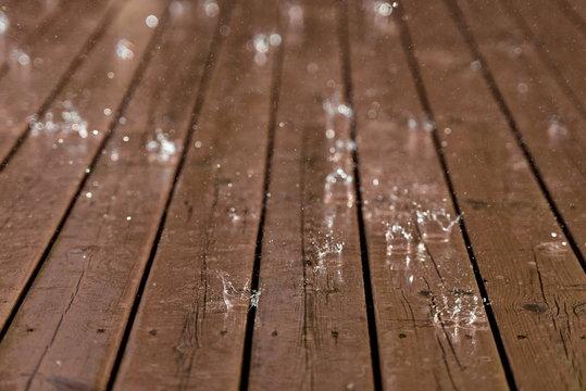 Rain from thunderstorm splash down on old worn wooden floor.