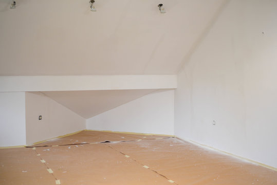 Basement with hanging wires and cardboard pieces on the floor for renovation