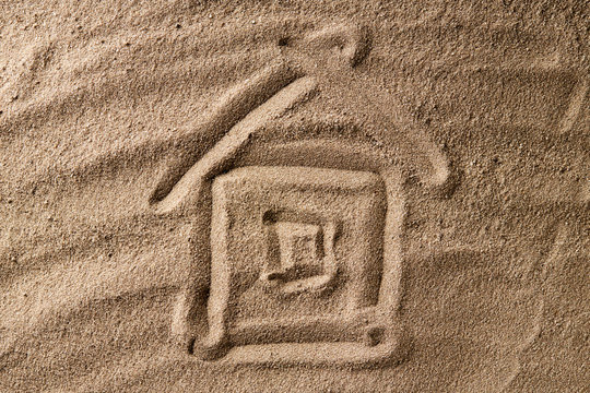 house symbol drawing on beach sand. hard shadow. property concept