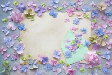 Decorative background with colored hydrangea flowers, paper for your text congratulations and an envelope.