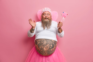 Horizontal shot of joyous funny man with thick beard and big fat belly, plays fairy on costume party, chills during spare time, sends positive vibes, works as animator, isolated over rosy background