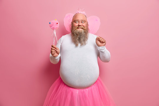 Positive plump man has fun on theme birthday party, feels like fairy who makes dreams come true, chills with children, has thick beard and fat belly, poses with magic wand and wings on back.