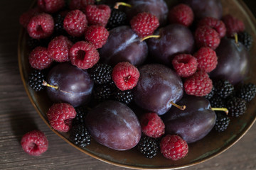 Raspberries, blackberries, plums in a bowl on a wooden background. Fragment, blur, selective focus.