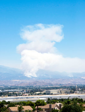 Wildfire smoke emerges from near Banning in the Apple fire of August 2020 in southern California.  The cities of Riverside and Moreno Valley are in the foreground