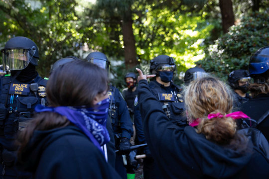 A woman gestures towards Portland Police officers following clashes during a protest in Portland