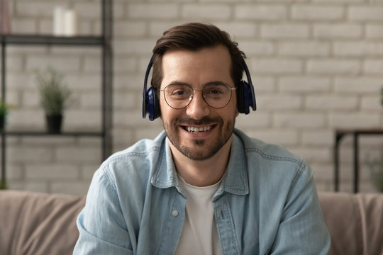 Close up headshot portrait of smiling man in headphones glasses have webcam conference at home office, profile picture of happy male in earphones speak talk on video call, virtual event concept