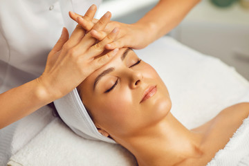 Cosmetologist making facial massage or treatment for young womans face in beauty spa salon