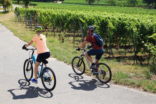 Symbolbild: Junges Paar bei einer Fahrradtour in den Weinbergen