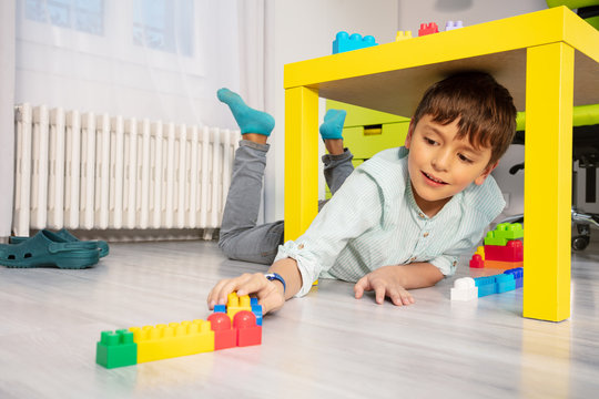 Boy play with blocks under table in kids room laying on the floor