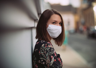 Young woman portrait putting on face mask outdoors virus allergy protection