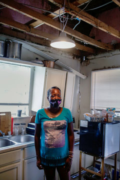 De Borah Wells poses for a photo as a collapsed ceiling and cracks in the walls are seen in her kitchen, in New Orleans