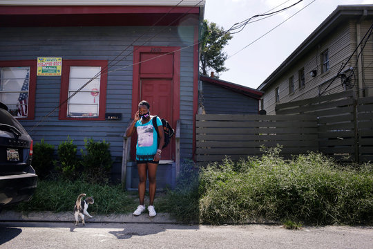 De Borah Wells stands outside her house with a collapsed ceiling and cracks in the walls, in New Orleans