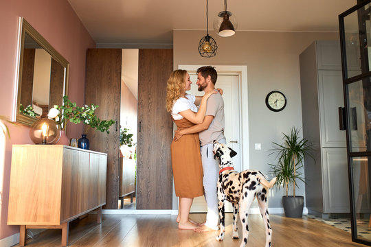 couple dancing slow dance, experiencing love at home. adorable dalmatian pet dog look at owners, relaxed time in living room