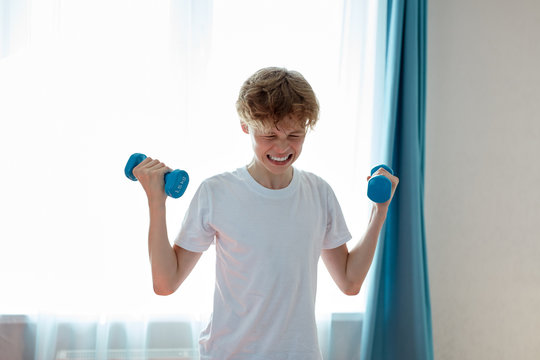 sportive child boy exercising with dumbbells at home, young caucasian teenager boy pump arm muscles