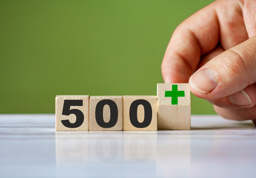 Hand turn wooden block with word 500+ (Polish government assistance program for children)