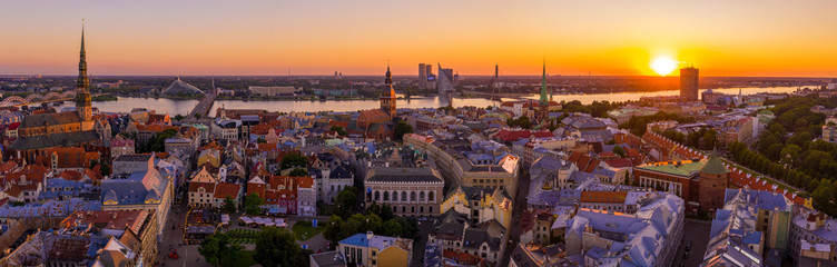 Panoramic shot of Riga covered in buildings under the sunlight during the sunset in Latvia