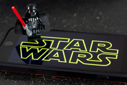 NEW YORK USA, APRIL 28 2019:  Darth Vader Lego Mini Figure with Star Wars wallpaper on an iPhone screen for Star Wars Day concept May the 4th Be With You