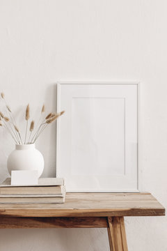 Portrait white picture frame mockup on vintage bench, table. Modern ceramic vase with dry Lagurus ovatus grass, books and busines card. White wall background. Scandinavian interior. Vertical.