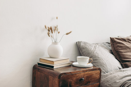 Modern white ceramic vase with dry Lagurus ovatus grass and cup of coffee on retro wooden bedside table. Beige linen and velvet pillows in bedroom. Scandinavian interior. Homestaging.