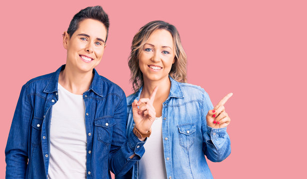 Couple of women wearing casual clothes with a big smile on face, pointing with hand finger to the side looking at the camera.