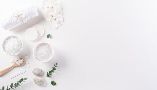Cosmetic bottle containers, skin cream with flowers. Natural beauty and spa concept, Top view on white table background.