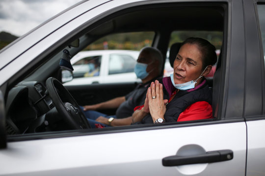 A woman wearing a face mask prays inside a car during a drive-in mass celebrated in a parking lot, amidst an outbreak of the coronavirus disease (COVID-19), in Chia