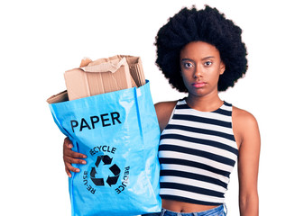 Young african american woman holding recycling bag with paper and cardboard thinking attitude and sober expression looking self confident