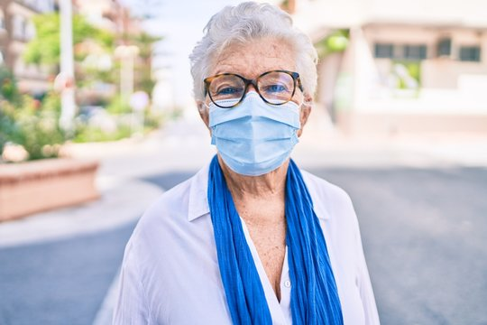 Elder senior woman with grey hair wearing coronavirus safety mask outdoors