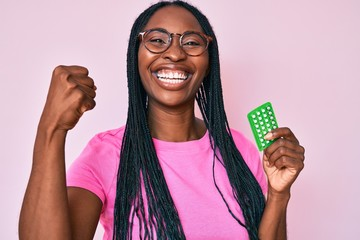 African american woman with braids holding birth control pills screaming proud, celebrating victory and success very excited with raised arms