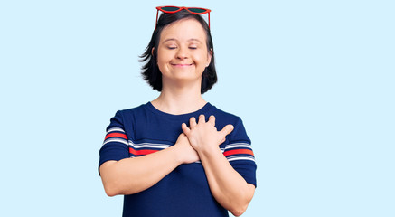 Brunette woman with down syndrome wearing casual clothes smiling with hands on chest with closed eyes and grateful gesture on face. health concept.