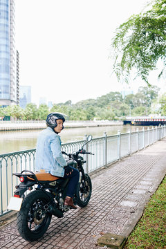 Serious Asian man in helmet riding on motorcycle along the river bank and looking away