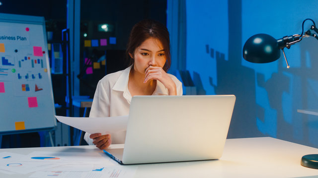 Freelance Asia women using laptop hard work in living room at house. Working from home overload at night, remotely work, self isolation, social distancing, quarantine for corona virus prevention.